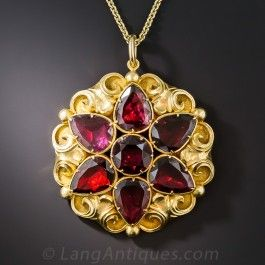 Measuring an impressive 1 5/8 inches diameter, this gorgeous Georgian jewel glistens front and center with lucky seven foil-backed garnets arranged in a striking star design. The gemstones gleam against a lavishly ornamented multidimensional background rendered in rich 18K yellow gold. This fabulous and fashionable antique treasure suspends from a new 24 inch chain.