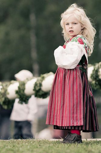A little Swedish girl on Midsummer Day (see the May pole waitng to be raised in the background)