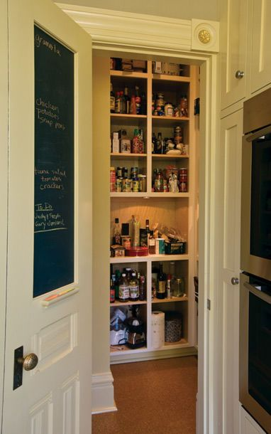 Neatly tucked between refrigerator and sink, a food pantry hides behind a narrow door with chalkboard paint that carries a perennial shopping list.