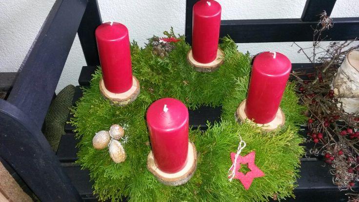 Adventskranz traditionell in rot gehalten, Kerzen auf Baumscheiben