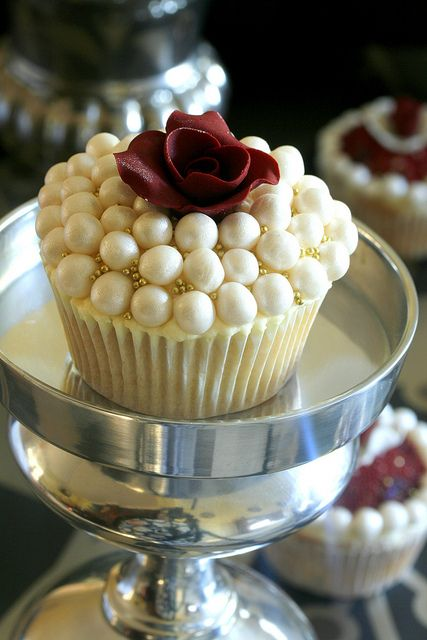 The combination of rolled fondant balls with luster dust and tiny gold dragees makes a great setting for a red rose.
