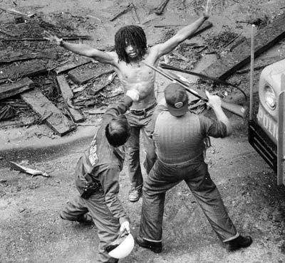In this image police are shown beating Delbert Africa of the MOVE organization after he surrendered during a confrontation in 1978. One policeman is shown winding up to hit Africa on the head with a steel helmet. In 1985, The Philadelphia Police ordered a bomb strike on a black organization living in the middle of a heavily populated black neighborhood. As the family members ran out of the burning house, they were repeatedly shot at and many of them were either killed or forced to run back…