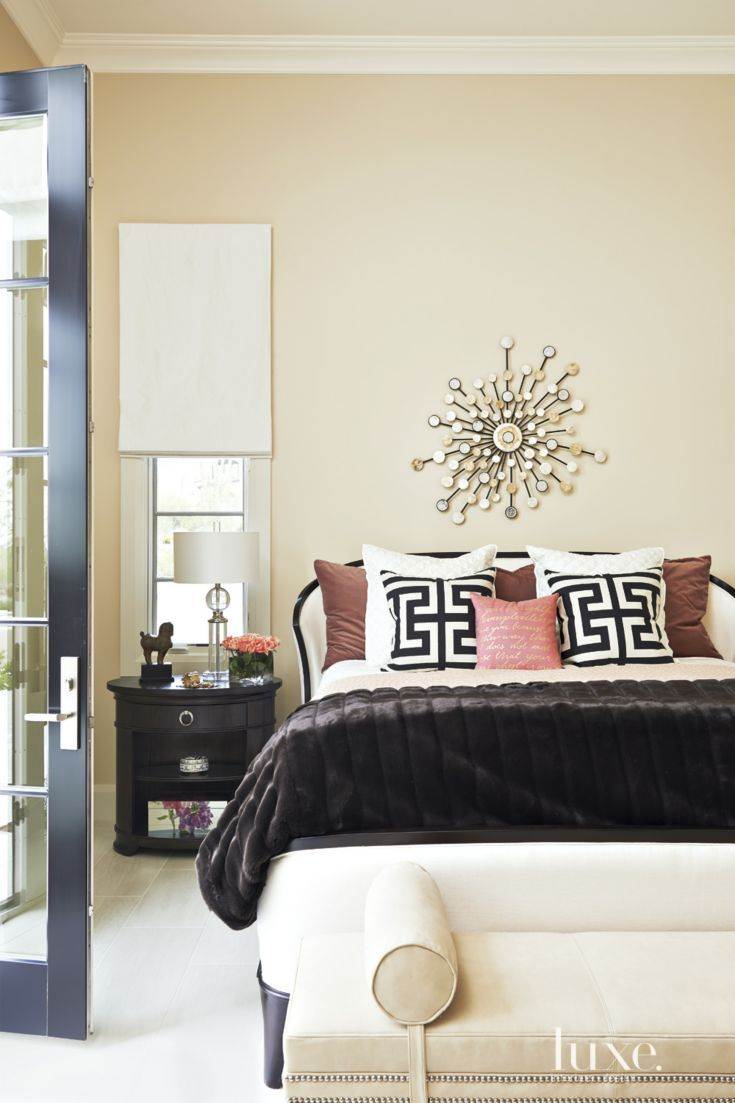 A tailored Harden Furniture bed and a nightstand by A.R.T. Furniture anchor one of the guest bedrooms. The geometric pillows are by Bassett Furniture and the leather bench is from Hickory Chair.