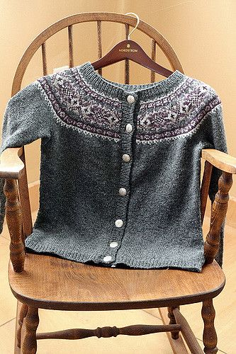 Knit seamlessly in the round from the bottom up, this simple, versatile, women's pullover/cardigan pattern features a classic XOXO stranded pattern in the 6-color yoke, with stars occupying the lozenge positions. The main color (charcoal) fades out to nearly white within the stranded pattern while, at the same time, a light purple darkens toward the center of the band. Hourglass waist shaping and fitted sleeves outline a flattering style to most sizes and shapes. The bottom band, button…