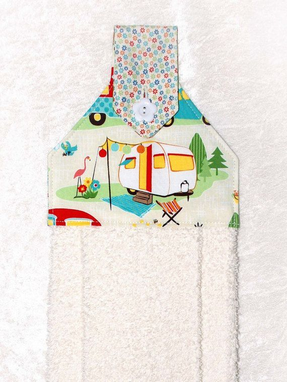 A cream hand towel with cheerful camper, flamingo and flowers. The plush cream towel is more luxurious than a standard kitchen towel. Featuring a designer fabric with a travel trailer on cream and charming floral fabric, it is sure to add fun to your home or camper kitchen and bath.  This handmade hanging towel works well buttoned over the handle of stove, dishwasher, drawer pull, or even a knob, door knob or vertical handle with optional hanging ring. It can even be used over a towel bar in…