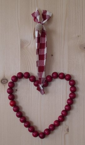 The red wooden beads on this heart shaped decoration have been scented with cinnamon oil so will make a fragrant addition to the home this Christmas.  It has a red and white check hanging loop. - http://www.oldeglory.co.uk/images/decorations/twigs/cinnamonbeadheart.jpg