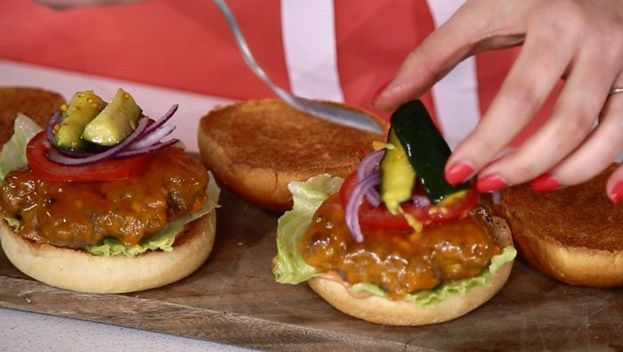 VIDEO! Learn how to make delicious, juicy cheeseburgers by pan-frying beef patties then finishing them off by steaming them. Then, pile them onto buns with sauce, salad and pickles and dig in...