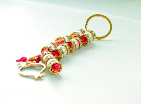 From a metal gold color metal ring ,hanged  a #pink satin cord with white and pink pearl beads , and silver plated crystal spacer #rondelle beads,  and  a metal gold pommegra... #keychain #brelock #keys #house #car #key #holder #holidays #christmas #ornament #pearls