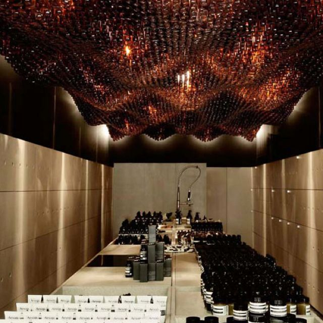 Ceiling, Glass bottles, backlit, retail, Aesop, small interior, dramatic, scale, organic, waves, movement, up-cycling