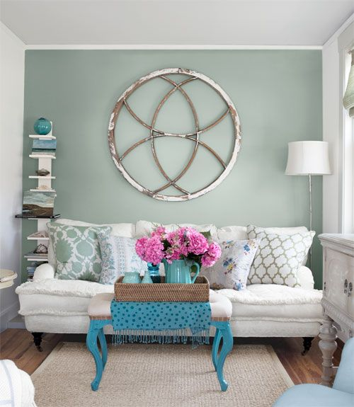 Love these colors, those pillows, the re-purposed ottoman, and the art above the couch is an old barn window!