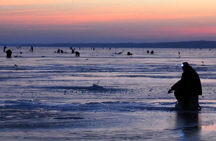 Un hombre usa un casco con lámpara mientras pesca en el hielo al amanecer en el lago Vileika, cerca a la villa Kasun, a 130 kilómetros al norte de la capital Minsk (Bielorrusia). (AFP/VANGUARDIA LIBERAL)