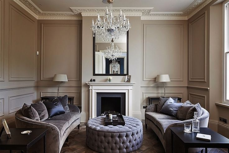 Gray and purple living room with trim moldings on taupe walls as well as ornate crown molding over parquet wood floors. Sophisticated living room features gray velvet sofas, facing each other, accented with gray velvet pillows and purple silk pillows paired with round purple tufted ottoman.