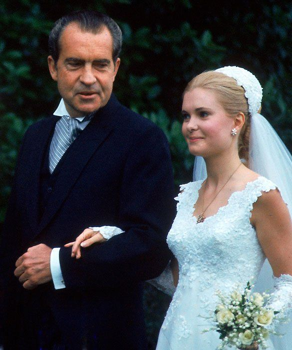 JUNE 12, 1971: The bride's father, President Richard Nixon, escorts Tricia to her wedding ceremony in the White House Rose Garden. She was wed to Edward Finch Cox wearing a Priscilla of Boston gown. Her younger sister, Julie Nixon Eisenhower, served as Matron of Honor.