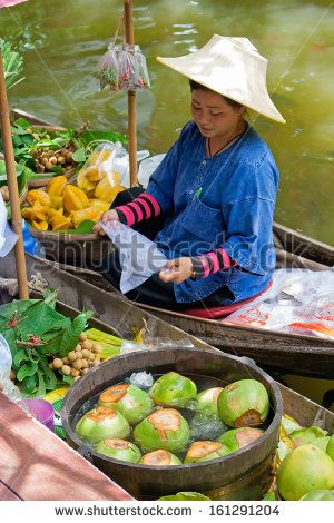 NAKORN PATHOM, THAILAND, JULY, 2011 - An unidentified woman sell her fruit on the boats at floating market, Nakorn Pathom, Thailand, July 2011. - stock photo