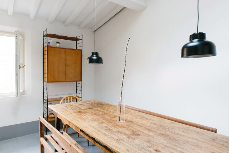 The charm of disparate elements—midcentury vintage, farmhouse furniture, and modern lighting—makes up the dining area in one of the apartments. On the table a Serax Water Bottle functions as a vase.