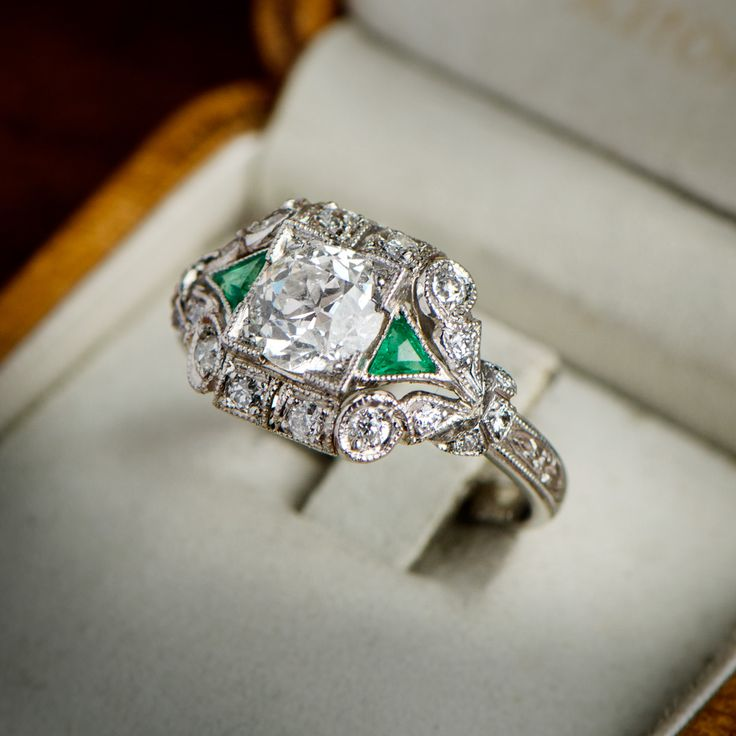 A beautiful diamond and emerald engagement ring. Available at Estate Diamond Jewelry.