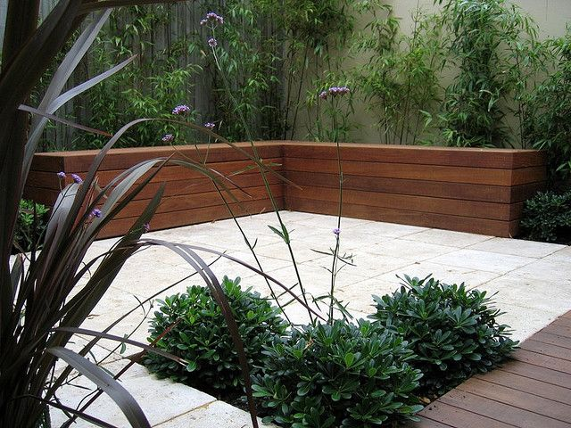 Courtyard Garden with Limestone Paving and Hardwood Deck and Bench Seating in this small courtyard garden is provided by a bespoke built-in bench, with an architectural backdrop of bamboo to screen the surrounding walls.