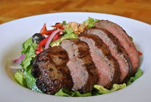 Menu Item: Marinated Flat Iron Steak with Pomegranate & Romaine Salad. It is tossed with avocado, candied almonds, red onions, Roma tomatoes, California olives & champagne chive vinaigrette.