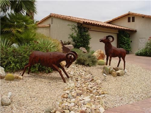 Sculpture and a dry stream bed make this former lawn into a low-care front garden. Isn't this more fun than a boring old postage stamp of grass? More lawn alternatives here: http://www.landscapingnetwork.com/lawns/alternatives.html