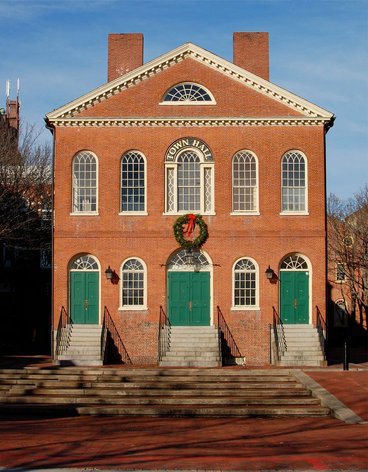 Old Town Hall in Salem, Massachusetts (dating from 1816-17). Features: Symmetrical facade; 6-over-6 double-hung windows with shutters; paneled door with elaborate surround (pediment, pilasters, sidelights, and fanlight); dentil molding or other decoration at cornice.