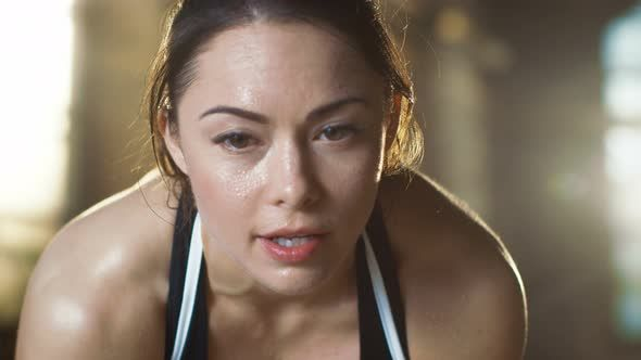 Beautiful Athletic Woman Wipes Sweat from Her Forehead with a Hand, Looks into Camera.