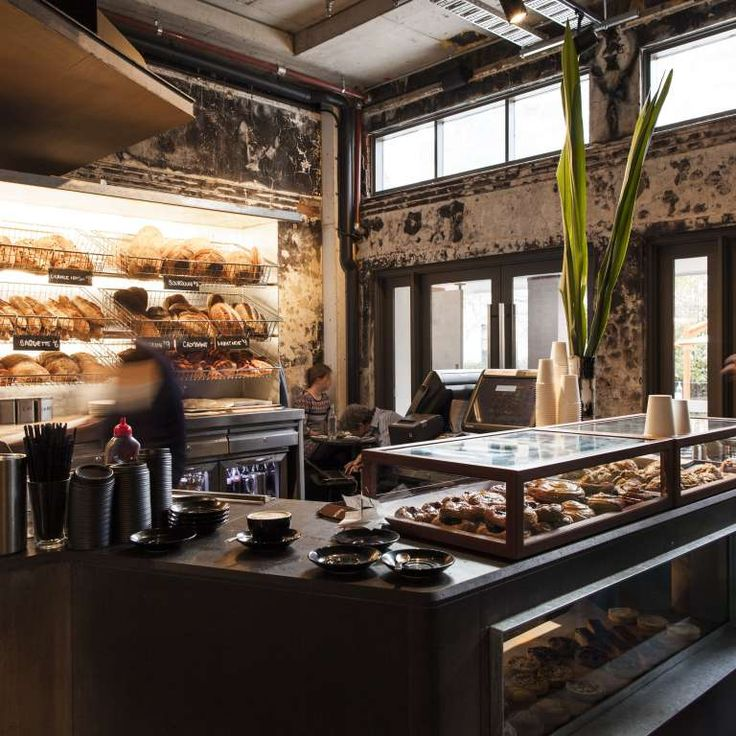 Cafe interior with racks of fresh bread and a display case full of pastries