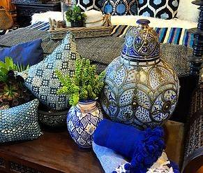 Layers of blue - Moroccan pottery, hand blockprint indigo pillows from India - silk velvet ikat from Uzbekistan - and rolled up cotton pompom blankets