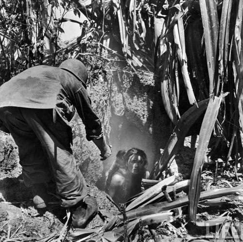 U.S. soldier helping frightened civilians out of caves where they had hidden during battle of Saipan, 1944.