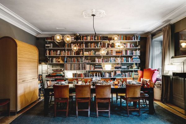 In the formal dining area, guests are invited to make themselves at home. The floor-to-ceiling bookcases create an intimate dining experience, which sits under original decorative ceiling details.