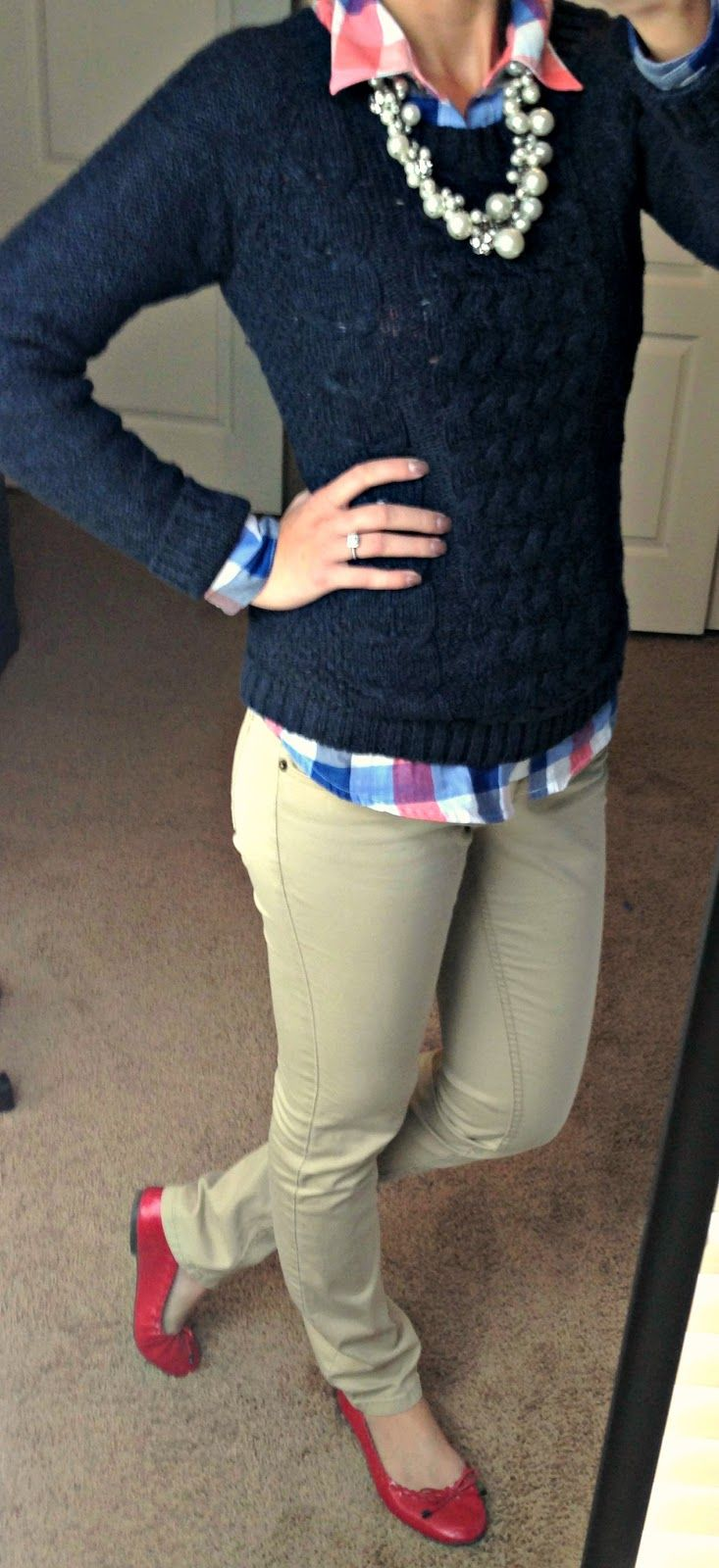 Large gingham shirt, statement necklace, navy cable knit, khakis, red flats. Cute!