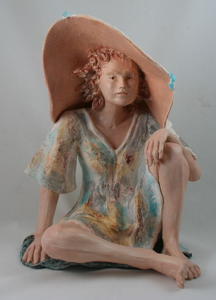 Seated female hand built using clay and finished with acrylic paint.  There is a blue bow on her hat.  See more barbarademaire.com