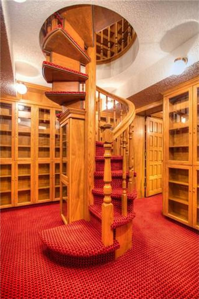 According to the floor plan, this is the study. I don't see room for the requisite minimum wingback leather chair, let alone a small reading desk.  I'd call it the lower library.  And also MY PRIVATE SPACE GO AWAY I'M WITH THE BOOKS, were it possible.