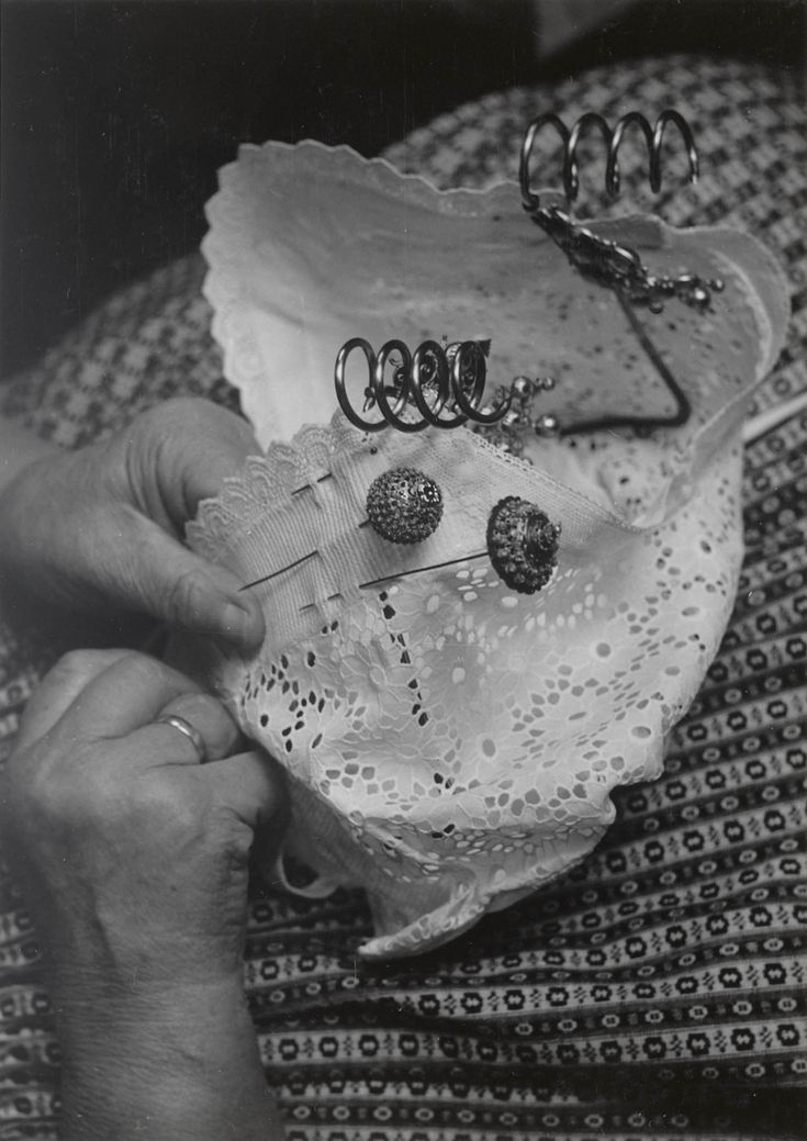 Mevrouw Teune-De Koning uit Middelburg, gekleed in de streekdracht van Nieuw- en St. Joosland, demonstreert het kapzetten.  Het plaatsen van de 'torenspelden' in de ondermuts. 1956 #Zeeland #NieuwStJoosland