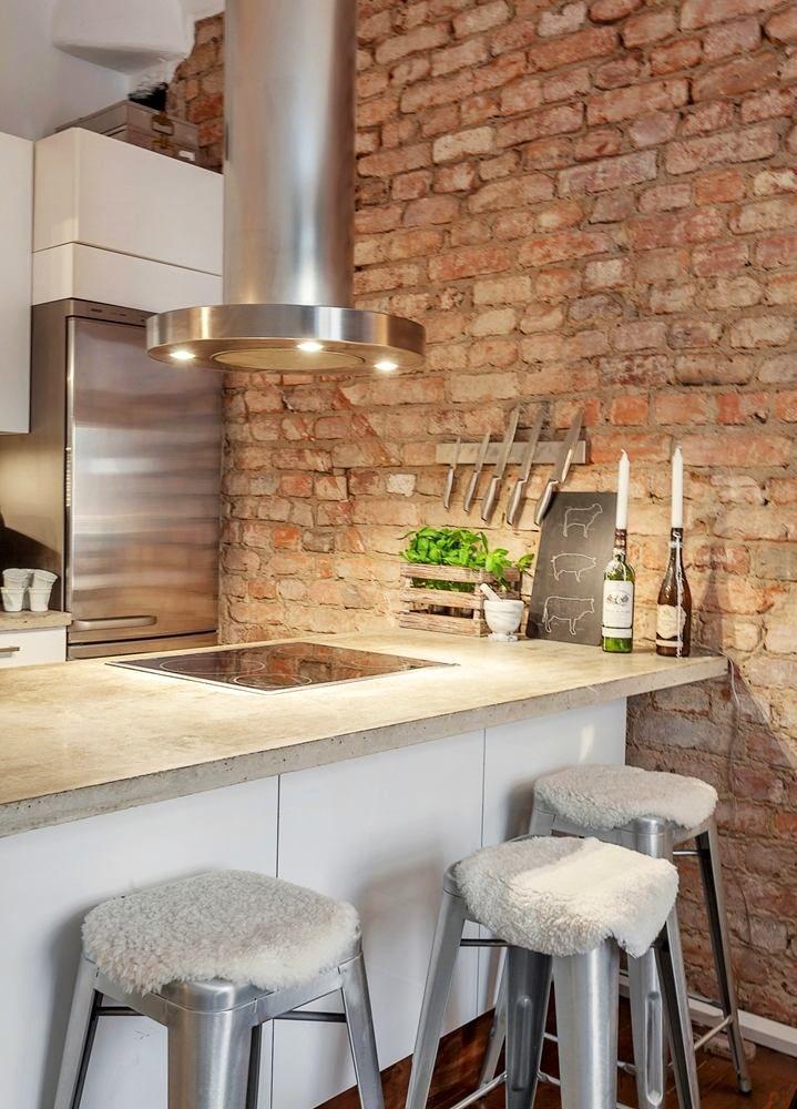 Фото из статьи: Маленькая квартира-студия с кирпичными стенами. ХОРОШО: большой и высокий стол для приема пищи.