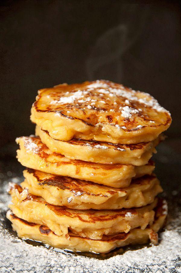 Pancakes à la pomme rapée- pour 16 pancakes 2 pommes moyennes, pelées, épépinées et râpées 200 g de farine 40 g de beurre fondu 20 cl de lait 1 œuf 1 yaourt au fromage blanc 1 gousse de vanille 1 c. à soupe de sucre en poudre 1 c. à café de bicarbonate alimentaire 1 pincée de sel Huile de tournesol (pour la cuisson) Sucre glace et miel (pour la dégustation)