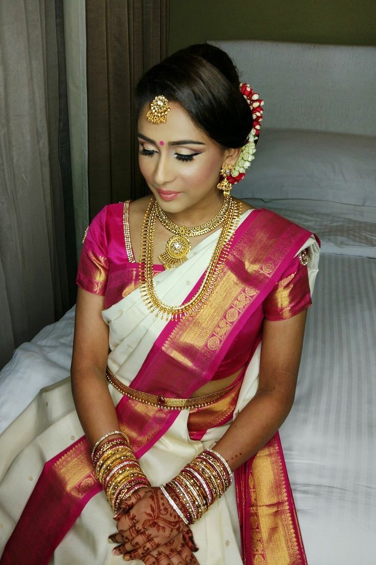 South Indian bride. Gold Indian bridal jewelry.Temple jewelry. Jhumkis.White and poink silk kanchipuram sari with contrast green blouse.Bun with fresh flowers. Tamil bride. Telugu bride. Kannada bride. Hindu bride. Malayalee bride.Kerala bride.South Indian wedding.