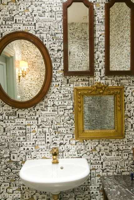 The toilet was made more interesting by adding several smaller mirrors for a quirky touch. #GoldFrameMirrors #Mirrors #OvalMirrors #PairOfMirrors #SmallBasin #VintageBasin #WallpaperedToilet