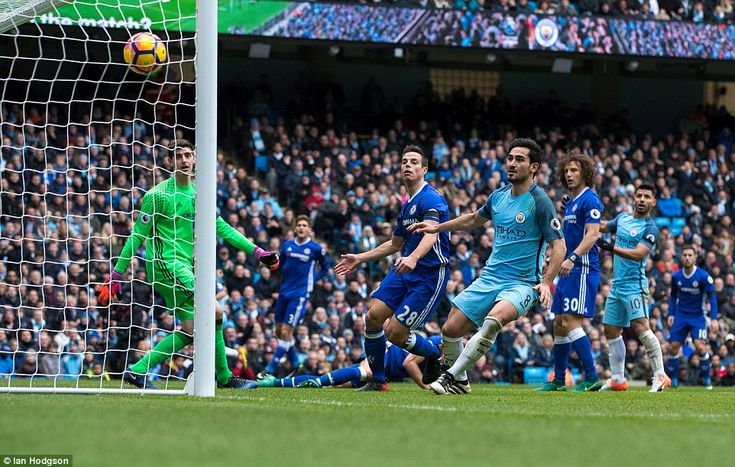 Thibaut Courtois andCesar Azpilicueta watch on as Gary Cahill deflects Jesus Navas' cross into his own goal in the first half