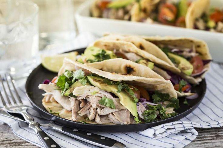 Recept voor gepocheerde kip-taco's voor 4 personen. Met zout, olijfolie, peper, kippenbout, rode kool, cherrytomaat, rode ui, avocado, kippenbouillon, koriander, limoen, witte wijnazijn en bloem