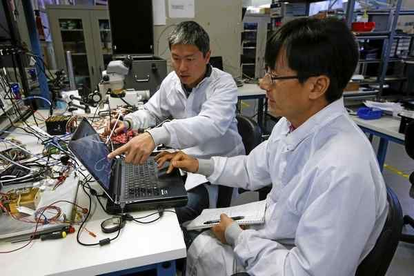 Engineers, from left, Billy Wahng and Jin Kim work on a Ka-Band radio for a satellite in an old converted car repair garage at Astro Digital in Mountain View on Tuesday.
