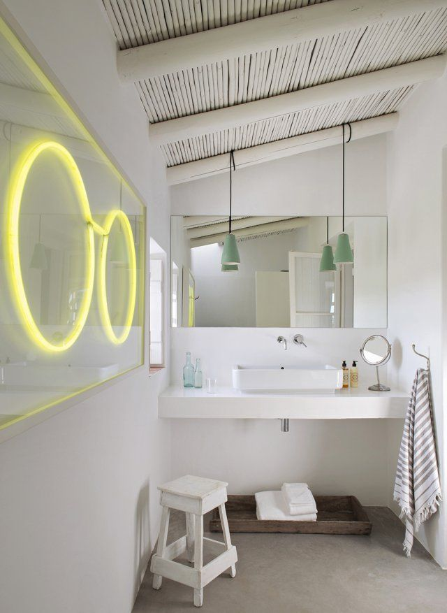 Une salle de bain tout en simplicité. Les six salles de bains de la maison sont équipées de vasque Roca. Un néon en forme de paire de lunettes, une ancienne enseigne d'opticien de Lisbonne dans les années 70, anime le mur.