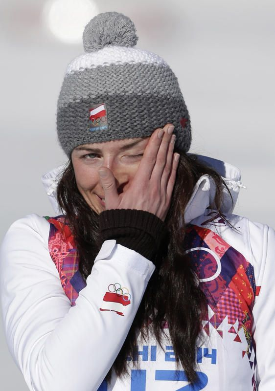 Poland's Justyna Kowalczyk celebrates winning the gold during the flower ceremony for the women's 10K classical-style cross-country race at the 2014 Winter Olympics, Thursday, Feb. 13, 2014, in Krasnaya Polyana, Russia. (AP Photo/Matthias Schrader)