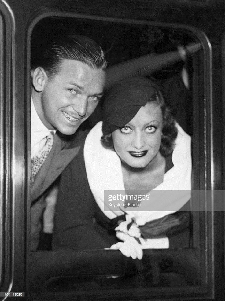 Joan CRAWFORD and Douglas FAIRBANKS junior looking out of their carriage window, prior to departure from Victoria station in London to Paris on July the 28th 1932.  (Photo by Keystone-France/Gamma-Keystone via Getty Images)