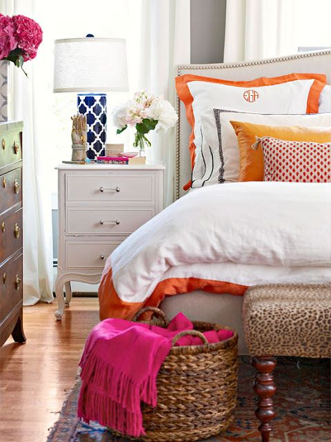 A white bedroom with blue, orange and pink pops of color. This space is so comfortable and stylish!