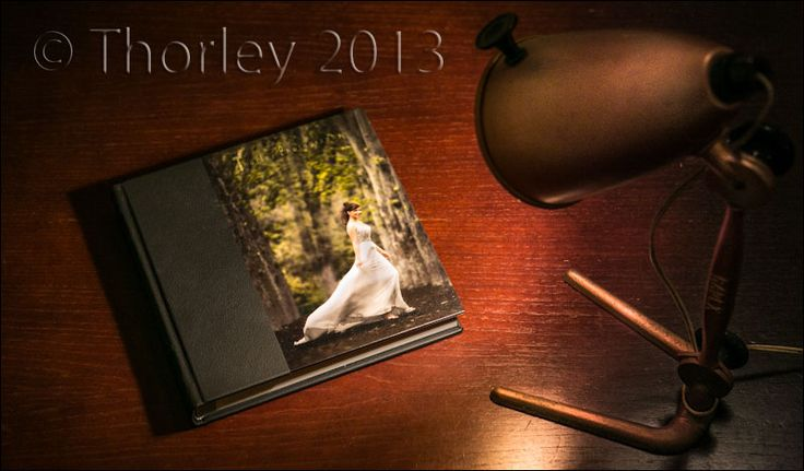 Wedding album on desk that is light with a spot light. The album cover features a beautiful your bride on a laminated cover print.