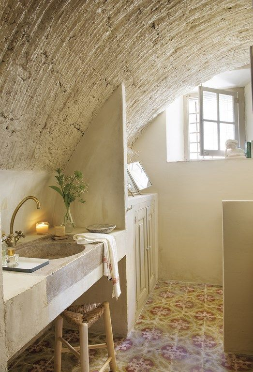 The curved ceiling again becomes the highlight in the renovated bathroom which also evokes a country style that is cosy and inviting. Rustic concrete in neutral cream tones are used here, and a beautiful printed floor adds colour and vibrancy in this space. The under-dressed window on the one end of the room should not be overlooked – it brings in an overflow of light and airiness into this bathroom.
