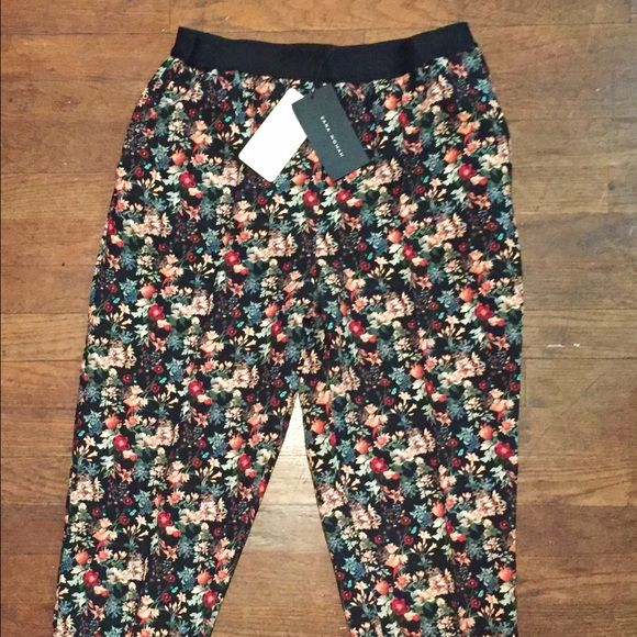 Zara Women floral trouser pant NWT sizeL Fall 2015 Zara size L floral trouser pant with elastic waist. Sits at natural waist with a cropped length hitting at the ankle. Loose fitting but tapered down the leg. I usually wear an 8 and I found these to be too big around the waist and hips. Ideal for a pear shaped figure. Cute floral pattern with black background. Never worn, perfect condition, new with tags. No trades. Zara Pants Trousers