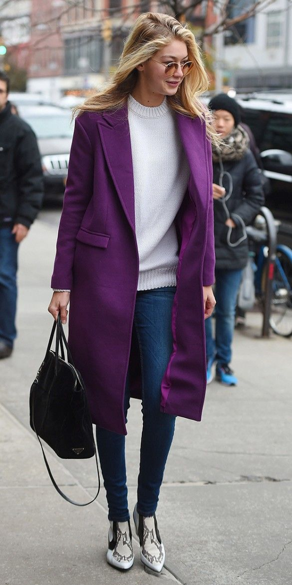 Gig Hadid look cold-weather chic in a long purple coat, cream seater, and snake-print boots.