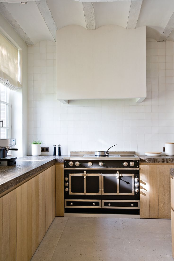La Cornue's Chateau 120 range cooker in black - looking chic paired with simple light wood cabinetry and stone countertop www.lacornue.com/en