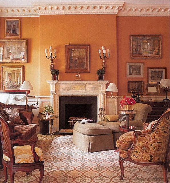 Beautiful pumpkin wall color that's repeated in the chairs and rug, carved mantel, art, beautiful moulding and furnishings
